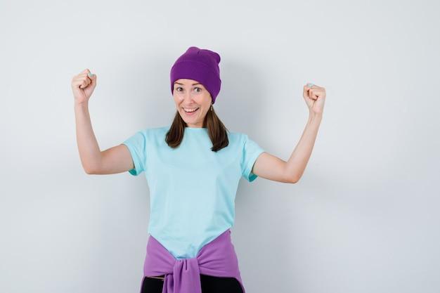 Jeune femme en t-shirt bleu, bonnet violet montrant le geste du gagnant et ayant l'air chanceux, vue de face.