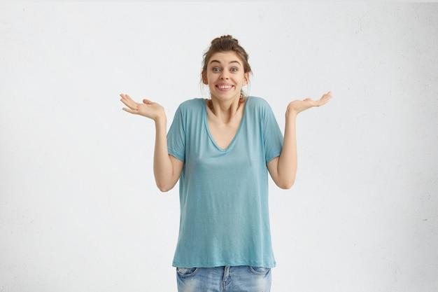 Jeune femme en t-shirt bleu et jeans en haussant les épaules n'ayant aucune idée de ce qu'il faut porter en fête