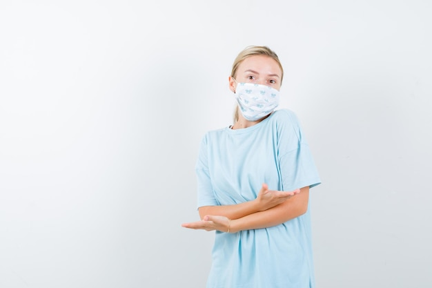 Jeune femme en t-shirt bleu avec un masque médical