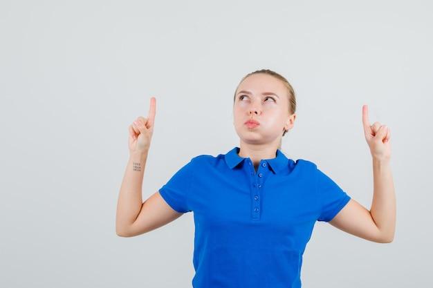 Jeune femme en t-shirt bleu pointant vers le haut et soufflant les joues
