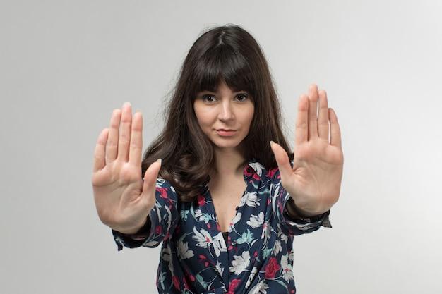 Jeune femme en t-shirt conçu avertissement avec les mains aux cheveux longs sur blanc