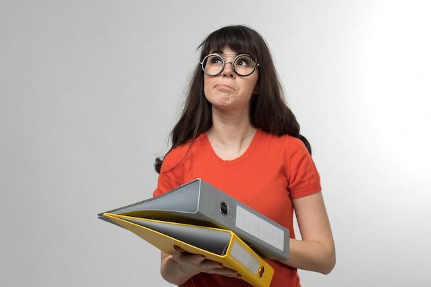 Jeune femme en t-shirt conçu contenant des fichiers sur blanc