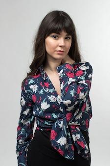 Jeune femme en t-shirt conçu posant avec des cheveux longs sur blanc