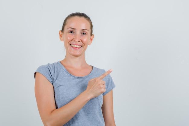 Jeune femme en t-shirt gris pointant vers le côté et à la joyeuse vue de face.