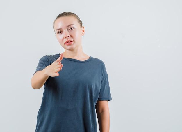 Jeune femme en t-shirt gris qui s'étend de la main pour trembler et à la convivialité