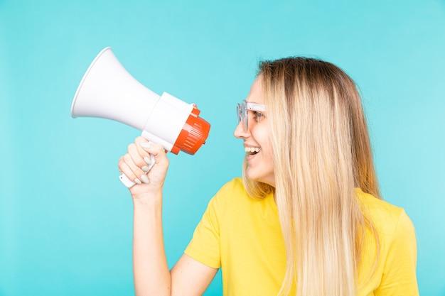 Jeune femme en t-shirt jaune sur mur bleu criant à travers un mégaphone et souriant
