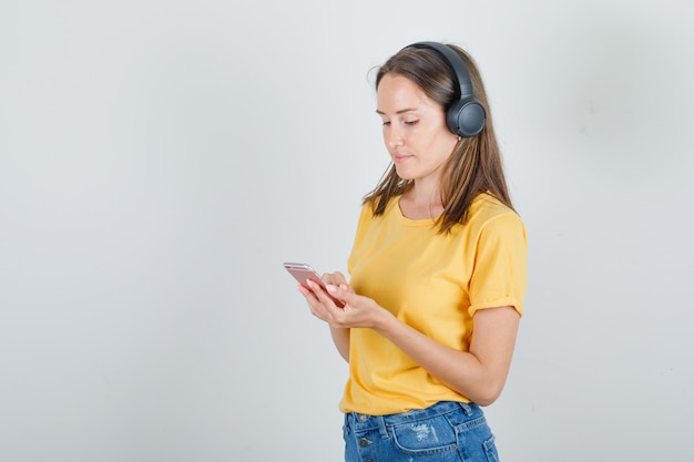 Jeune femme en t-shirt jaune, short, écouter de la musique avec des écouteurs