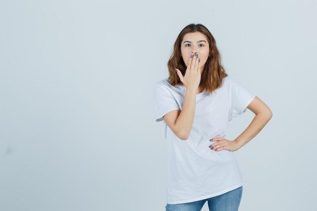 Jeune femme en t-shirt, jeans tenant la main sur la bouche et regardant étonné, vue de face.