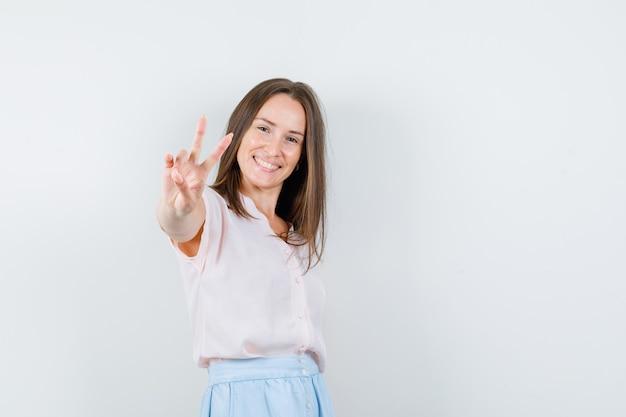 Jeune femme en t-shirt, jupe montrant le signe de la victoire et à la vue de face positive.