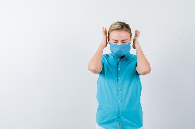 Jeune femme en t-shirt, masque gardant les mains de manière agressive et semblant ennuyée