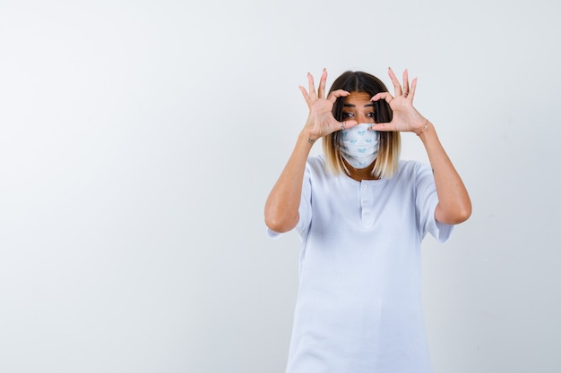 Jeune femme en t-shirt, masque montrant le geste de lunettes et à la jolie vue de face.