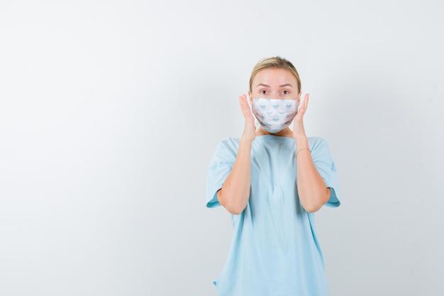 Jeune femme en t-shirt, masque tenant la main près du visage et l'air perplexe