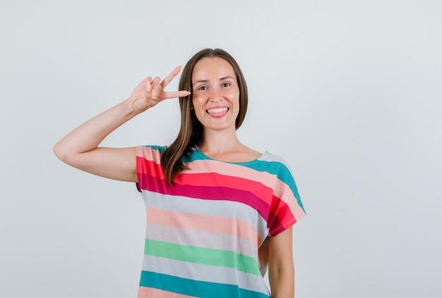 Jeune femme en t-shirt montrant v-sign et à la vue de face, heureux.