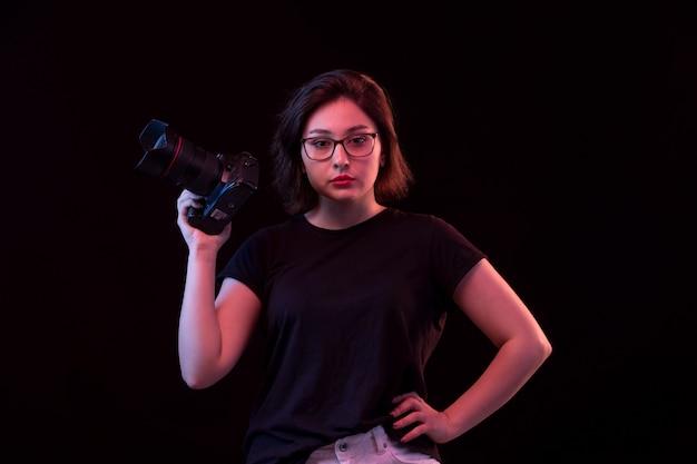 Jeune femme en t-shirt noir avec appareil photo