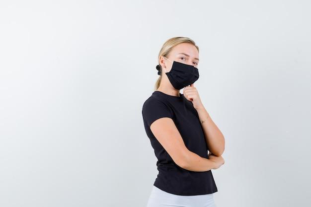Jeune femme en t-shirt, pantalon, masque médical debout en pensant pose isolée