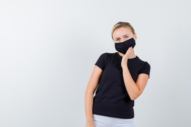 Jeune femme en t-shirt, pantalon, masque médical tenant la main sur le masque et l'air perplexe