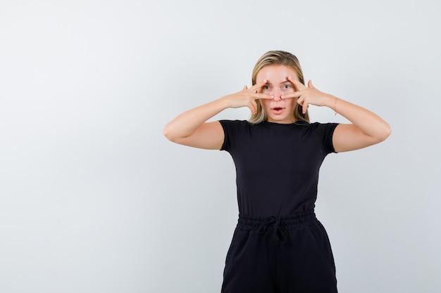Jeune femme en t-shirt, pantalon montrant des signes de victoire sur les yeux et l'air confiant, vue de face.