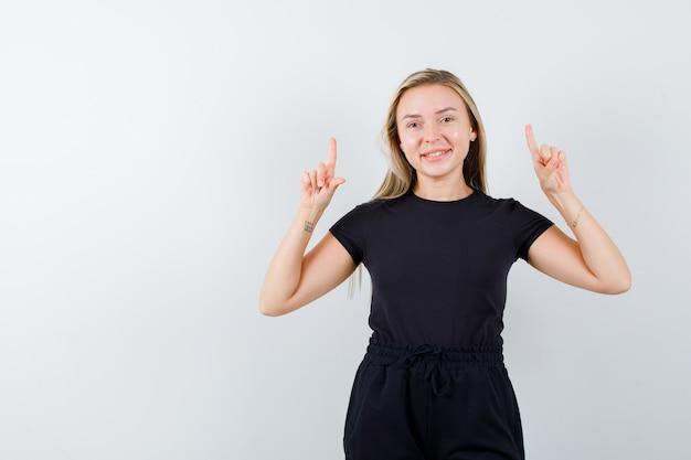 Jeune femme en t-shirt, pantalon pointant vers le haut et à la joyeuse vue de face.