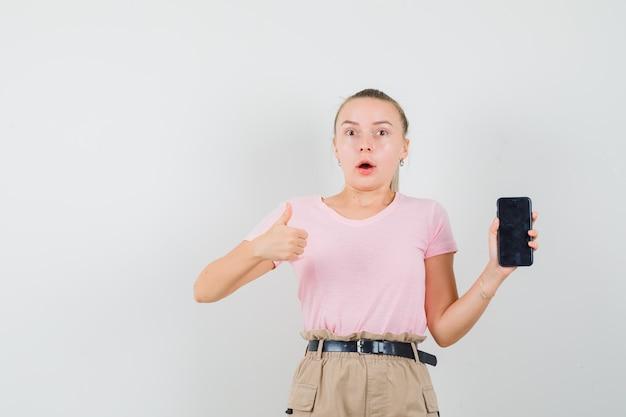 Jeune femme en t-shirt et pantalon tenant un téléphone mobile, montrant le pouce vers le haut et à la surprise