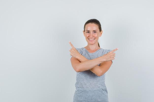 Jeune femme en t-shirt pointant vers le côté et à la joyeuse vue de face.