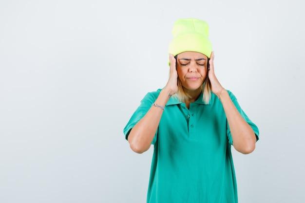 Jeune femme en t-shirt polo, bonnet avec les mains près du visage, fermant les yeux et regardant concentré, vue de face.