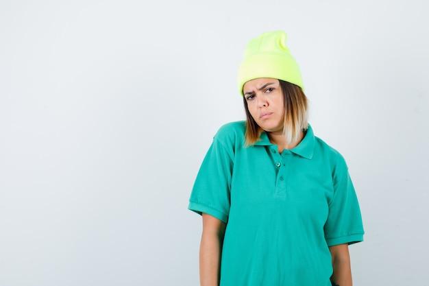 Jeune femme en t-shirt polo, bonnet regardant la caméra et regardant grincheux, vue de face.