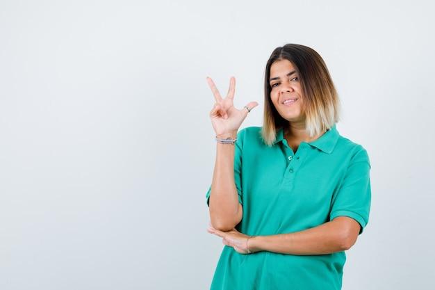 Jeune femme en t-shirt polo montrant le geste de la victoire et l'air heureux, vue de face.