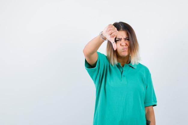 Jeune femme en t-shirt polo montrant le pouce vers le bas avec des joues gonflées et l'air insatisfait, vue de face.