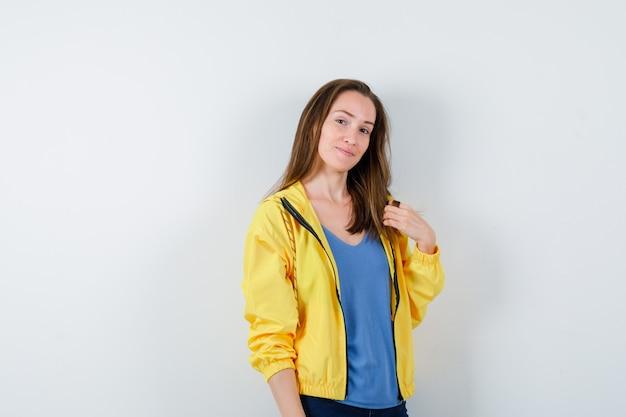 Jeune femme en t-shirt posant en regardant la caméra et en ayant l'air confiant, vue de face.