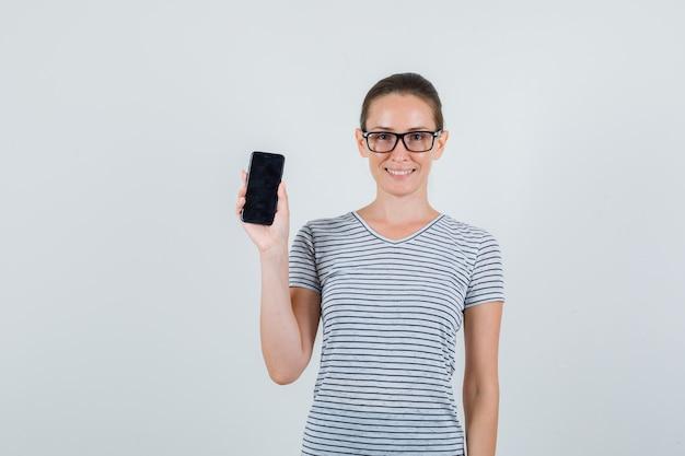 Jeune femme en t-shirt rayé, lunettes tenant un téléphone portable et à la vue de face, heureux.