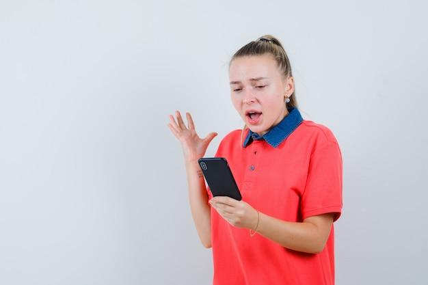 Jeune femme en t-shirt à la recherche de téléphone mobile et à l'excitation