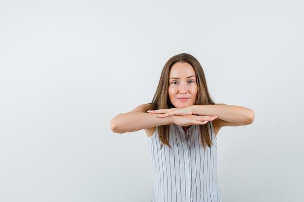 Jeune femme en t-shirt regardant la caméra en se couchant sur les mains et regardant curieux, vue de face.