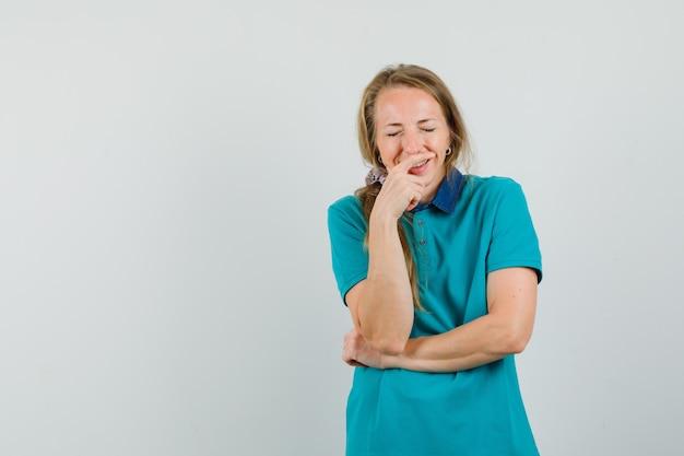 Jeune femme en t-shirt en riant fort et à la joyeuse