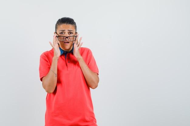 Jeune femme en t-shirt rouge décollant des lunettes et à la jolie vue de face.