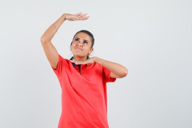 Jeune femme en t-shirt rouge montrant le geste de la danse traditionnelle et à la jolie vue de face.