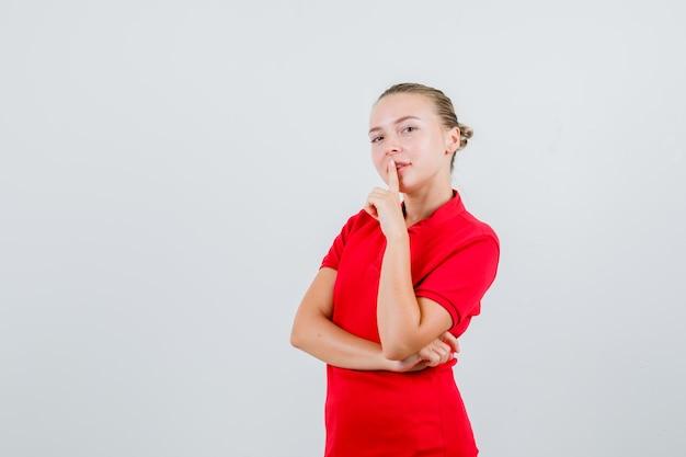 Jeune femme en t-shirt rouge montrant le geste de silence et à la prudence
