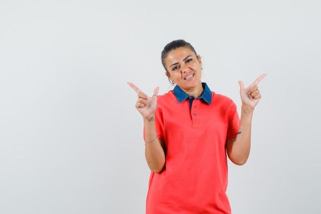 Jeune femme en t-shirt rouge pointant vers différentes directions avec l'index et à la jolie vue de face.
