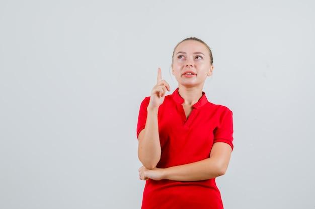 Jeune femme en t-shirt rouge pointant vers le haut et à la recherche concentrée