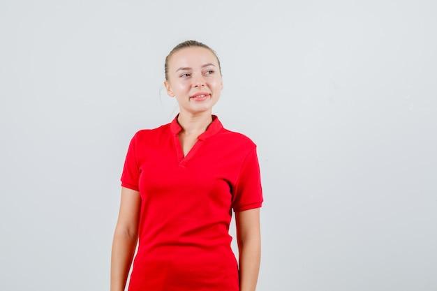 Jeune femme en t-shirt rouge à la recherche de suite et à l'optimiste