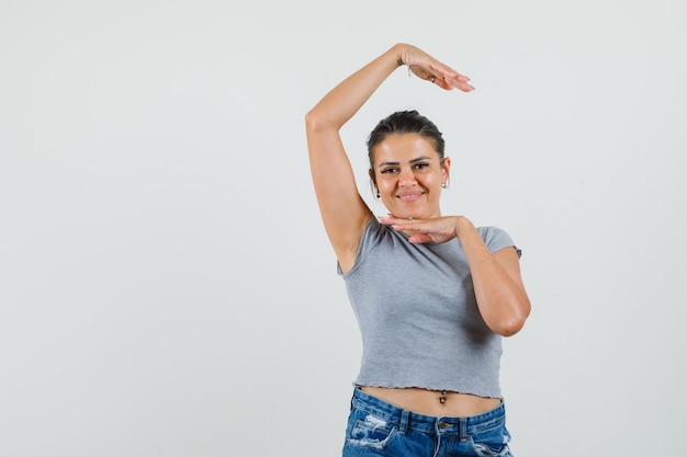 Jeune femme en t-shirt, short montrant le geste de la danse traditionnelle et à la fringante