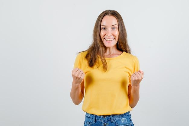 Jeune femme en t-shirt, short montrant le geste du gagnant et à la joyeuse