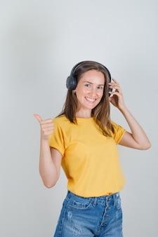 Jeune femme en t-shirt, short touchant les écouteurs avec le pouce vers le haut et à la joyeuse