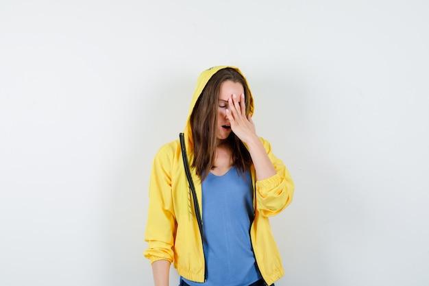 Jeune femme en t-shirt tenant la main sur le visage et à l'oubli, vue de face.