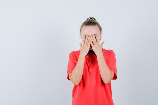 Jeune femme en t-shirt tenant les mains sur le visage et à la gêne