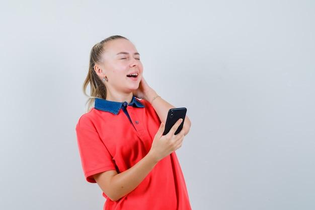 Jeune femme en t-shirt tenant un téléphone mobile et à la recherche de plaisir