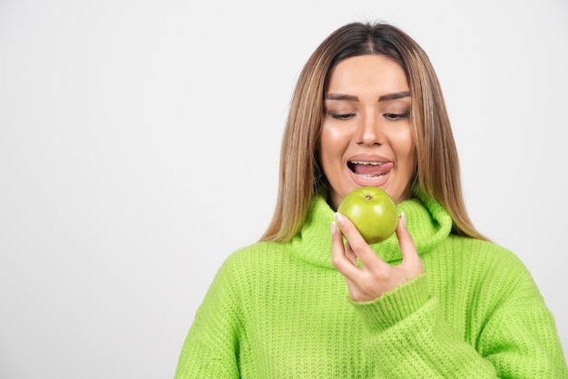Jeune femme en t-shirt vert mangeant une pomme