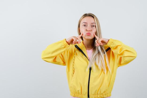 Jeune femme en t-shirt, veste en appuyant sur les joues soufflées avec les doigts et à la jolie
