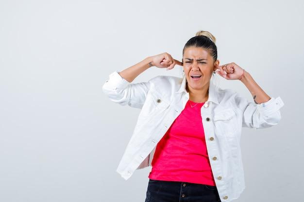 Jeune femme en t-shirt, veste blanche bouchant les oreilles avec les doigts et ayant l'air de s'ennuyer, vue de face.