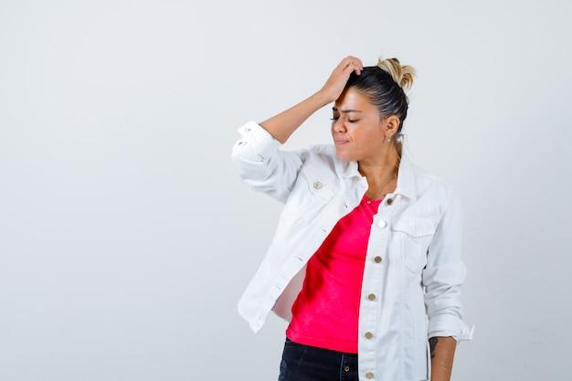 Jeune femme en t-shirt, veste blanche avec la main sur la tête et l'air oublieux, vue de face.