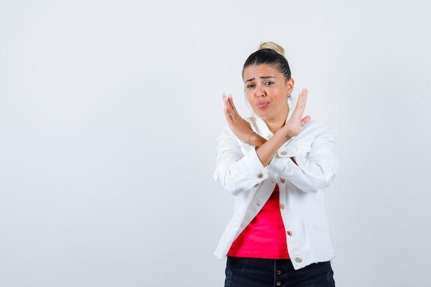 Jeune femme en t-shirt, veste blanche montrant un geste de refus et l'air insatisfaite, vue de face.